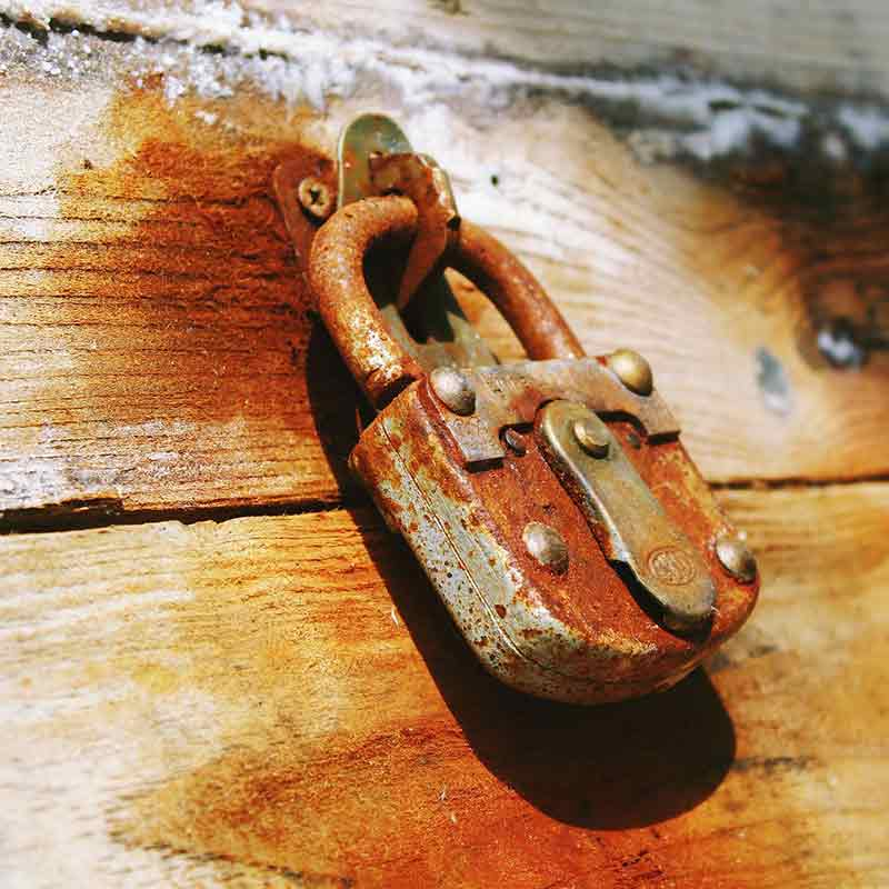 An old padlock on a wooden box to illustrate security with WordPress care and hosting