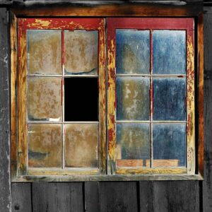 A distressed and broken window with red and orange peeling paint which needs to be fixed
